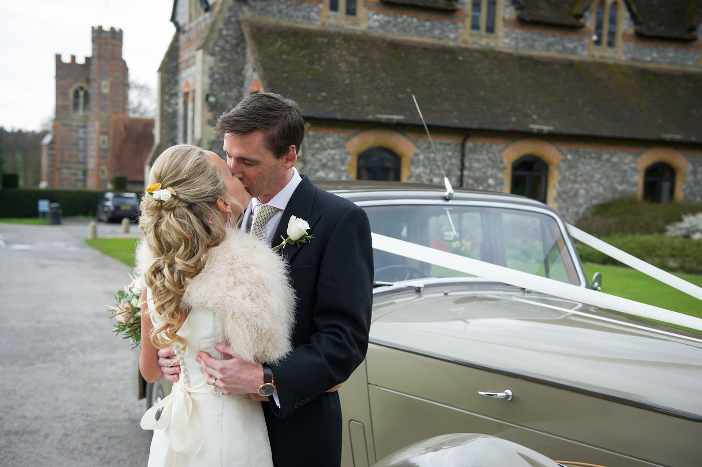 Bride & Groom Wedding Photograph Kissing Next To Car - Hair & Makeup For Bride in Berkshire, Surrey & surrounding areas